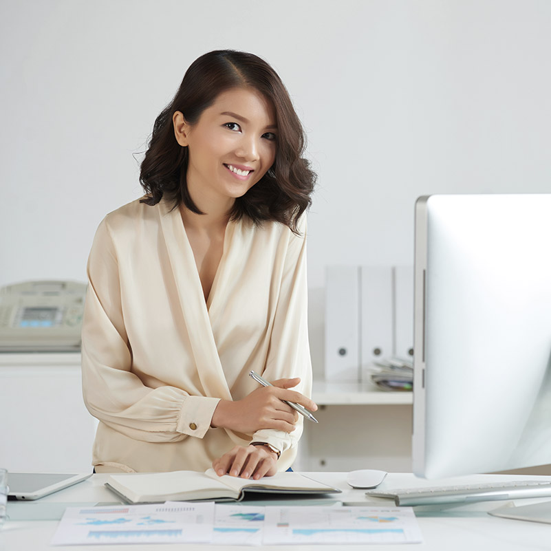 Portrait of beautiful Asian woman woman smiling at camera while working at office desk